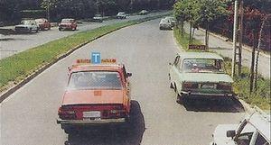 Az osztott pályás úton Ön vezeti a tanulókocsit. A jobbrattási kötelezettség értelmében a zöld taxi melletti elhaladás után le kell-e húzódnia a tanulókocsinak az úttest szélére?